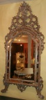 Ornately carved wood framed mirror in a silver finish