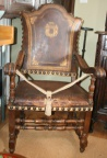 Rare early 18th century Continental armchair in original leather with an armorial design. Walnut wood frame.