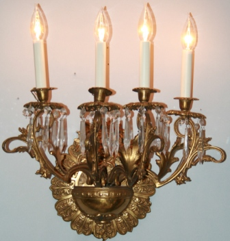 One of a pair of antique four arm well detailed brass wall sconces with dangling crystals.